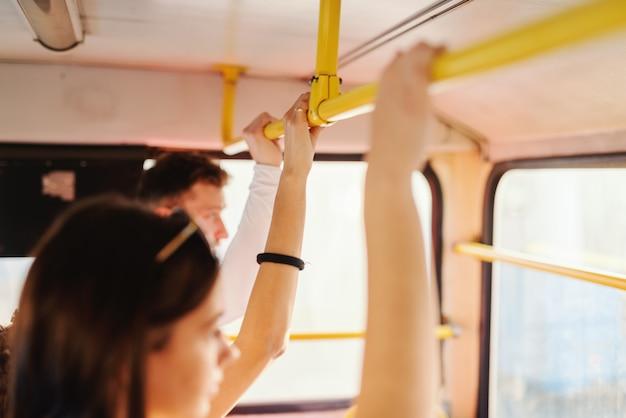 Viajantes segurando o punho no transporte público.