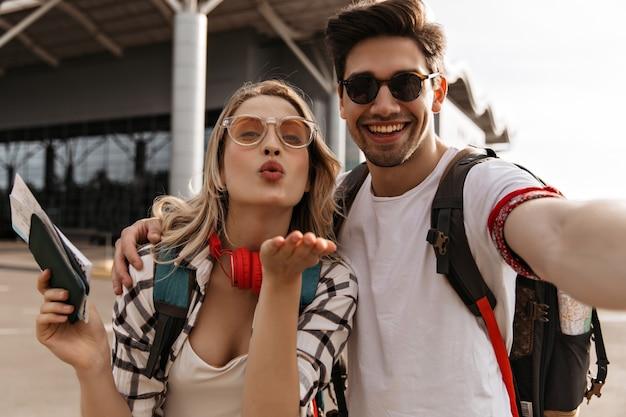 Viajantes tirando selfie perto do aeroporto