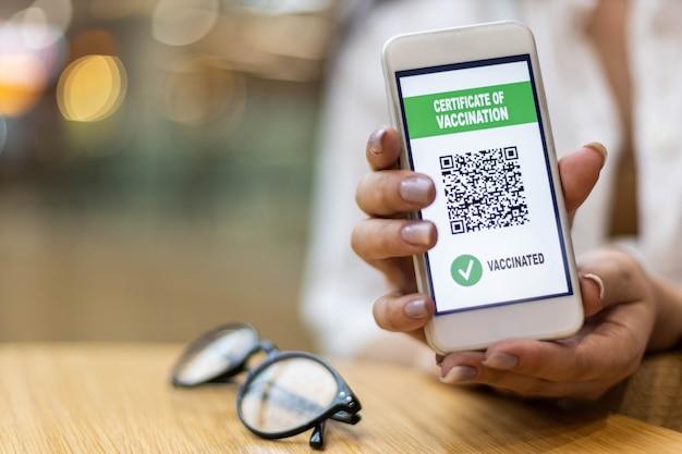 Viajar com as mãos femininas segurando um smartphone com certificado eletrônico de vacinação na tela