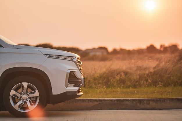 Viajar de carro branco estacionado no fundo por do sol estrada