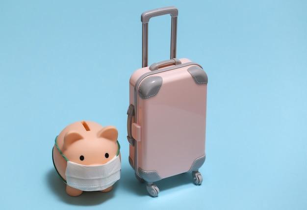 Viajar durante covid-19. mini mala de viagem de plástico e cofrinho com máscara facial em fundo azul.
