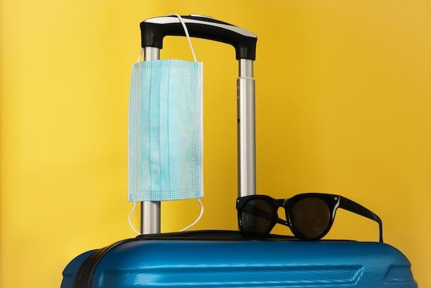 Viajar durante o tempo de covid-19. máscara médica, mala, óculos de sol no fundo amarelo. férias, feriados nos tempos da coroa.