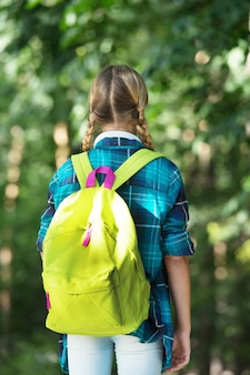 Viajar é descobrir. criança carrega uma bolsa de viagem natural ao ar livre. destino de viagem. férias de verão. férias escolares. viajar e viajar. viajar é divertido.