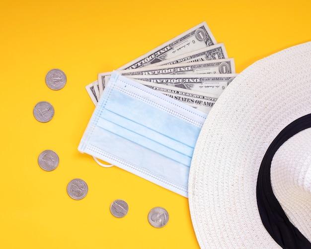 Viajar em 2020 com máscara dinheiro chapéu moedas fundo amarelo, não há mais para covid-19