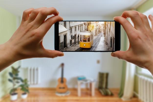 Viajar em casa. viagem online a lisboa, portugal via smartphone. lendário bonde amarelo na tela