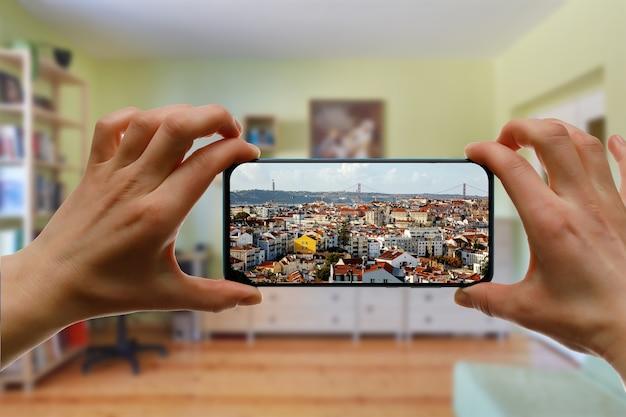 Viajar em casa. viagem online a lisboa, portugal via smartphone. paisagem urbana na tela.