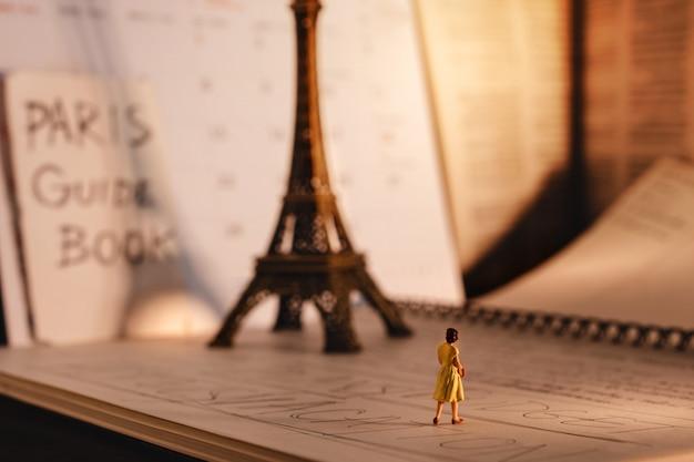 Viajar em paris, frança. uma mulher de turista em miniatura, olhando para a torre eiffel