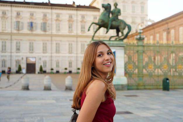 Viajar na europa. garota atraente na itália com o palácio real de turim ao fundo.