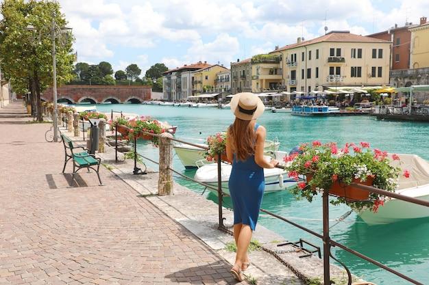 Viajar na itália. vista traseira da menina bonita da moda apreciando a visita ao lago de garda. férias de verão na itália.