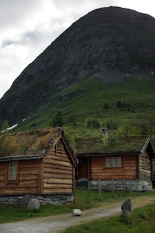 Viajar para a noruega, casas com telhados cobertos de grama erguem-se no sopé da montanha.