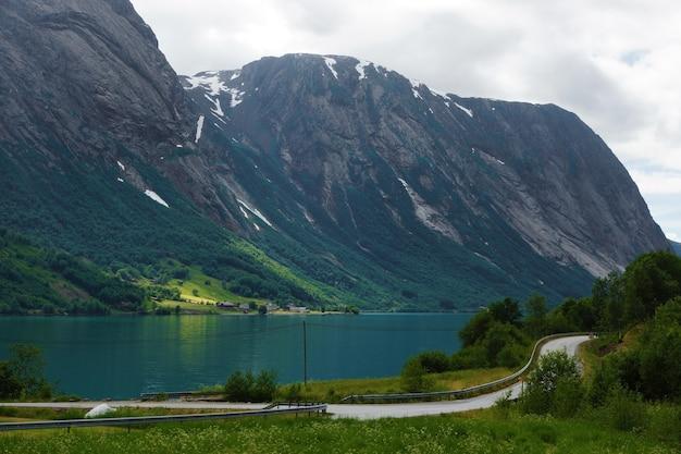 Viajar para a noruega, o rio da montanha azul flui entre as montanhas, ao longo da costa há uma estrada.