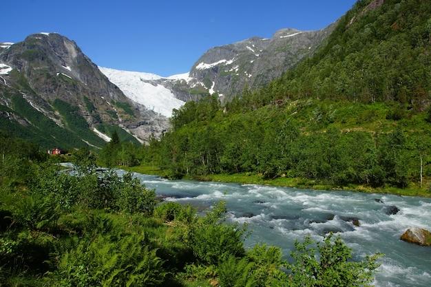 Viajar para a noruega, o rio da montanha azul flui entre pedras e arbustos de uma alta montanha com uma geleira.