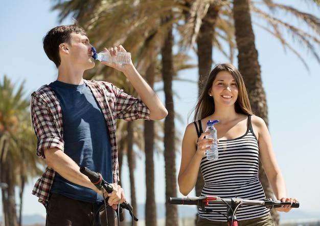 Viajar por ciclos casal bebendo de garrafas plásticas