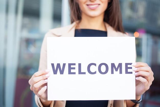 Viajar por. negócios de mulheres com o cartaz com mensagem de boas-vindas.