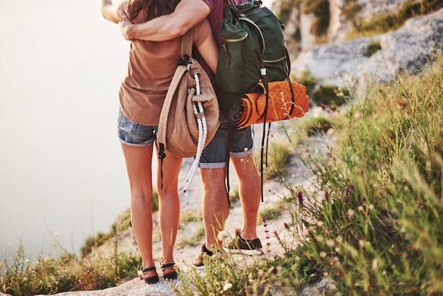 Viajar precisa de equipamento. o jovem casal decidiu passar as férias de forma ativa na beira de uma linda rocha com um lago ao fundo.