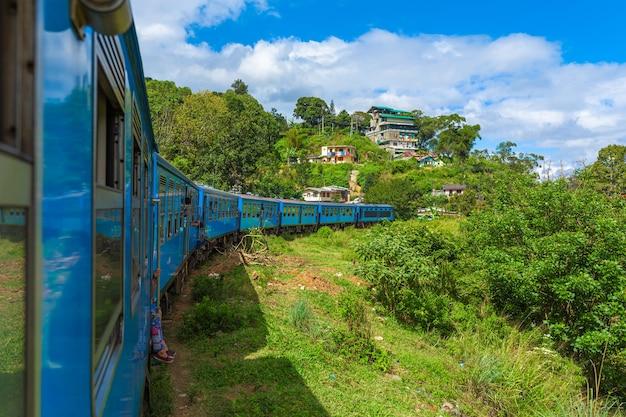 Viaje de trem público ao redor da ilha de sri lanka. o trem viaja por montanhas e plantações de chá. estrada de ferro cênica