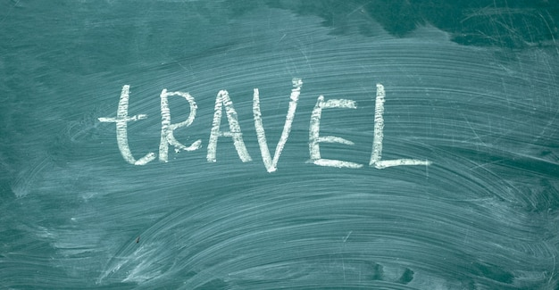 Viaje escrito à mão com giz branco em um quadro-negro verde.