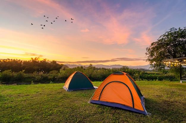 Viaje para espalhar a tenda em um amplo espaço aberto à noite