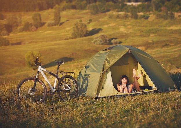 Viaje sozinho de bicicleta. jovem mulher na tenda