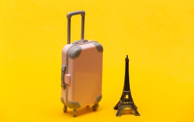 Viajou para paris. mini mala de viagem de plástico e estatueta da torre eiffel em fundo amarelo.