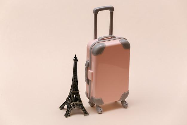 Viajou para paris. mini mala de viagem de plástico e estatueta da torre eiffel em fundo bege.