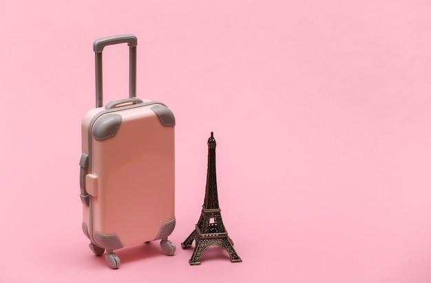 Viajou para paris. mini mala de viagem de plástico e estatueta da torre eiffel em fundo rosa.