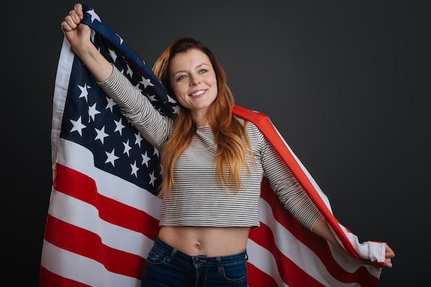 Vibrações americanas. linda garota magnética e doce posando com uma bandeira enquanto trabalhava em uma sessão de fotos e isolada em um fundo cinza
