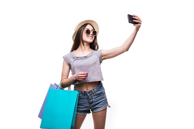 Vibrações coloridas de compras. retrato de mulher morena com chapéu e roupas brilhantes com sacolas de compras coloridas, tirando selfie com smartphone