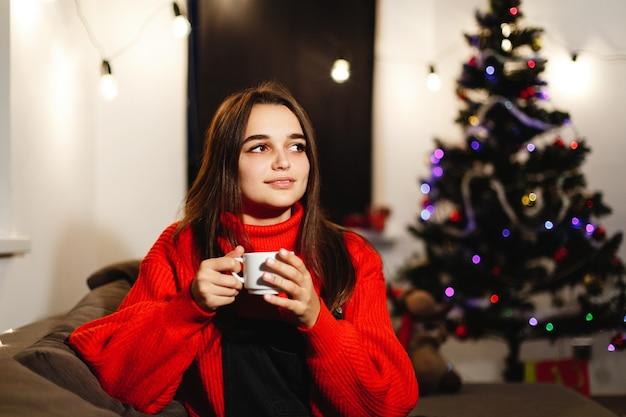 Vibrações de natal e ano novo. decorações para casa. encantadora mulher jovem na camisola vermelha