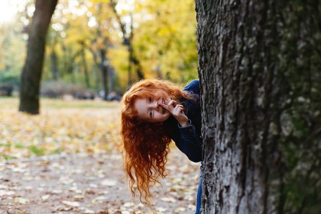 Vibrações de outono, retrato de criança. cabelo encantador e vermelho menina parece feliz andando e jogando em t