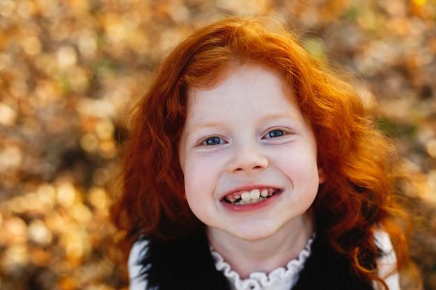 Vibrações de outono, retrato de criança. cabelo encantador e vermelho menina parece feliz em pé sobre o caído