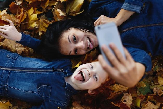 Vibrações de outono, retrato de família. encantadora mãe e sua filha de cabelo vermelho se divertir tomando uma selfie em sm