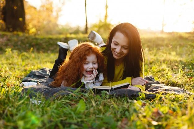 Vibrações de outono, retrato de família. mãe encantadora e sua filha de cabelo vermelho se divertir sentado sobre o caído