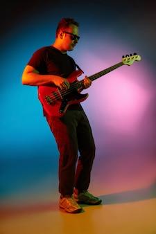 Vibrante. jovem músico inspirado e expressivo, guitarrista atuando em um fundo gradiente colorido em luz de néon. conceito de música, hobby, festival, arte. artista alegre, retrato colorido e brilhante.