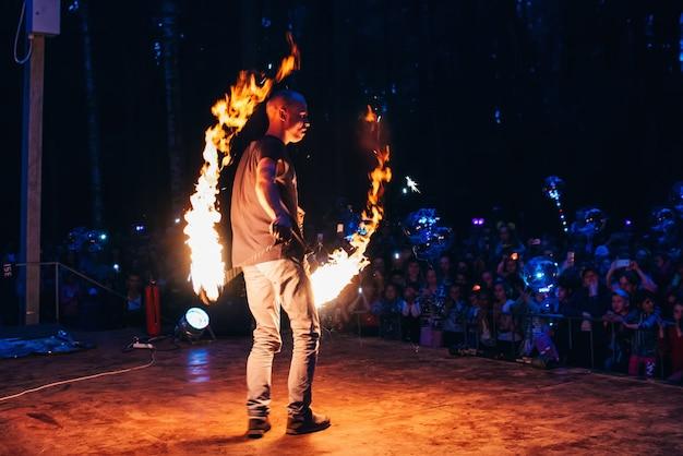 Vichuga, rússia - 17 de junho de 2018: show de fogo, um faquir homem acenando tochas