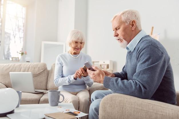 Viciado em gadgets. agradável casal de idosos sentado na sala de estar colado em seus gadgets