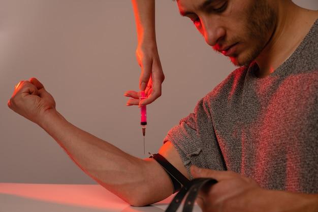 Viciado em homem desleixado, esperando a dose de heroína, a mão da mulher segura a seringa acima da mão