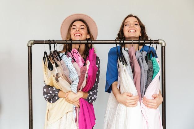 Viciados em compras consideravelmente jovens mulheres escolhendo roupas.