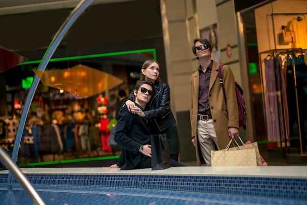 Viciados em compras encantadores com sacos de papel discutindo algo que a serra no shopping