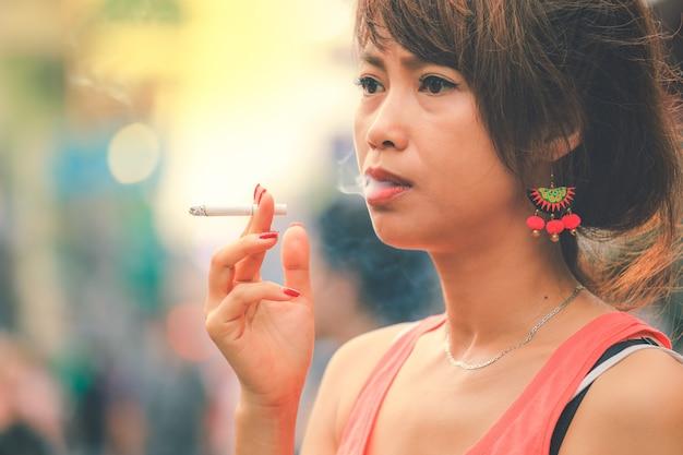 Vício de mulher asiática estressado fumando um cigarro em estilo vintage