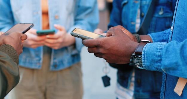 Vício em internet. visão aproximada da empresa de pessoas multirraciais em pé no círculo e concentrando-se em seus gadgets enquanto passam o tempo na internet