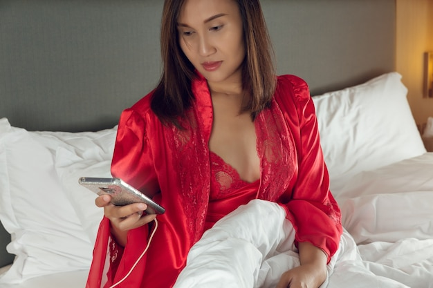 Vício em smartphone, mulher asiática sentada na cama à noite em uma camisola de cetim e um robe vermelho com um telefone celular no quarto. menina em roupa de dormir usando um smartphone tarde da noite porque está insone