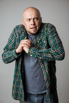 Vicioso homem emocional na camisa posando sobre parede bege