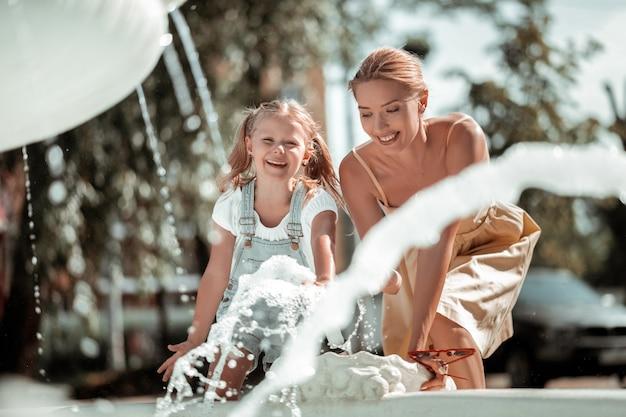 Vida amorosa. menina alegre se divertindo brincando com a mãe com os salpicos de água da fonte.