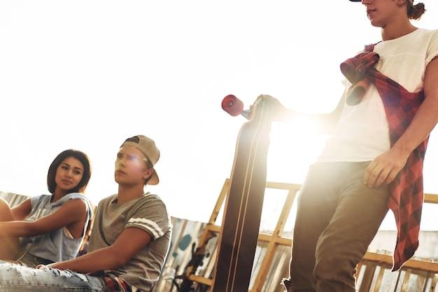 Vida cheia de amizade. grupo de jovens modernos saindo juntos enquanto passam o tempo na pista de skate ao ar livre