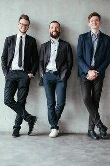 Vida corporativa moderna. equipe profissional alegre. homens confiantes e bem-sucedidos em roupas casuais elegantes