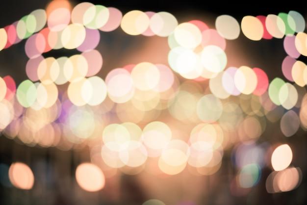 Vida da cidade de noite desfocado: carros, pessoas e lâmpadas de rua, estilo retro