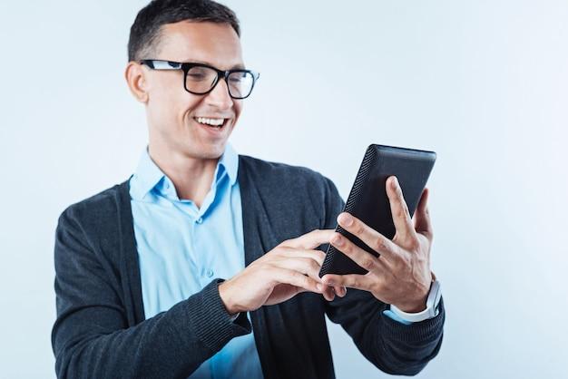 Vida inovadora. foco seletivo em um computador tablet segurado por um homem maduro e animado navegando na internet e sorrindo amplamente ao fundo.