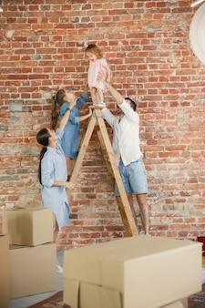 Vida nova. a família adulta mudou-se para uma nova casa ou apartamento. cônjuges e filhos parecem felizes e confiantes. movimento, relações, conceito de estilo de vida. brincando juntos, preparando-se para consertar e rindo.