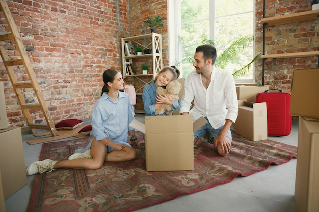 Vida nova. família adulta mudou-se para uma nova casa ou apartamento. cônjuges e filhos parecem felizes e confiantes. movimento, relações, conceito de estilo de vida. desempacotar caixas com suas coisas, brincar juntos.